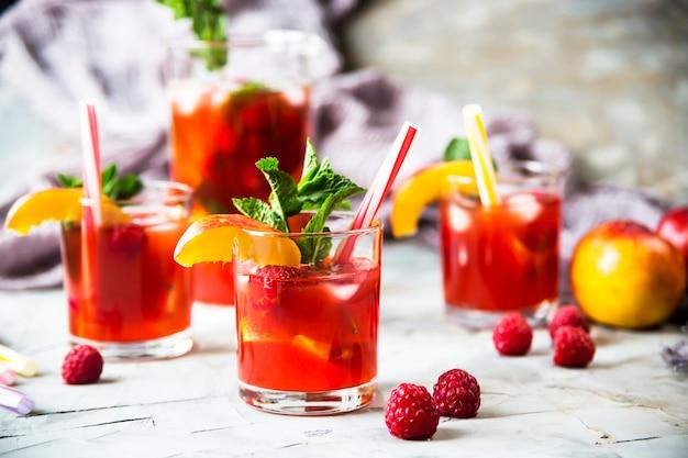 Leichtes sommererfrischungsgetränk mit früchten und beeren - sangria. in gläsern auf einem grauen tisch