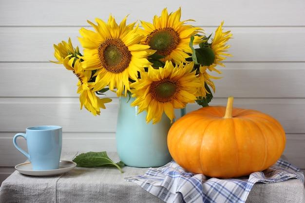 Leichtes stillleben mit einem strauß sonnenblumen und einem kürbis auf dem tisch. ernte, fülle. rustikales interieur.
