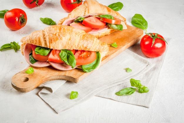Leichtes und herzhaftes frühlingsfrühstück. croissant mit schinken, käse, frischen tomaten und basilikum. auf einem weißen steintisch mit den zutaten. kopieren sie platz