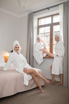Leichtigkeit. lächelnde hübsche frau, die barfuß in bademantel und handtuch auf dem bett sitzt, und glückliche freundinnen in der nähe des fensters im spa am nachmittag?