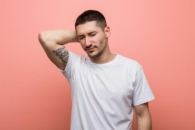 Leiden nackenschmerzen des jungen zufälligen mannes wegen des sitzenden lebensstils.