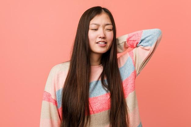 Leidende nackenschmerzen der jungen kühlen chinesischen frau wegen des sitzenden lebensstils.