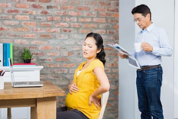 Leidende schwangere frau, die zu hause auf stuhl während ehemannlesezeitung sitzt