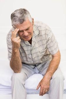 Leidender älterer mann, der zu hause seine stirn berührt