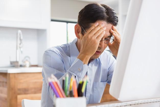 Leidender mann mit den händen auf dem gesicht, das am schreibtisch mit computer auf ihm sitzt