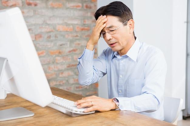 Leidender mann mit der hand auf dem gesicht zu hause, das vor computer sitzt