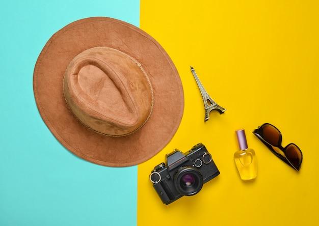 Leidenschaft für reisen, fernweh-konzept. reise nach frankreich, paris. filzhut, filmkamera, sonnenbrille, parfümflasche, andenkenstatue des eiffelturm-layouts auf einem farbigen papierhintergrund. flach liegen.
