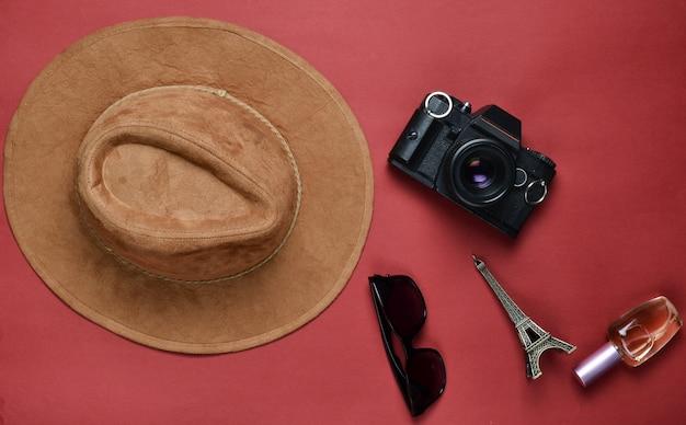 Leidenschaft für reisen, fernweh-konzept. reise nach frankreich, paris. filzhut, filmkamera, sonnenbrille, parfümflasche, andenkenstatue des eiffelturm-layouts auf einem roten papierhintergrund. flach liegen.