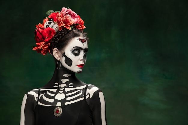 Leidenschaftlich. junges mädchen wie santa muerte saint death oder sugar skull mit hellem make-up. porträt lokalisiert auf dunkelgrünem studiohintergrund mit exemplar. feiern von halloween oder tag der toten.