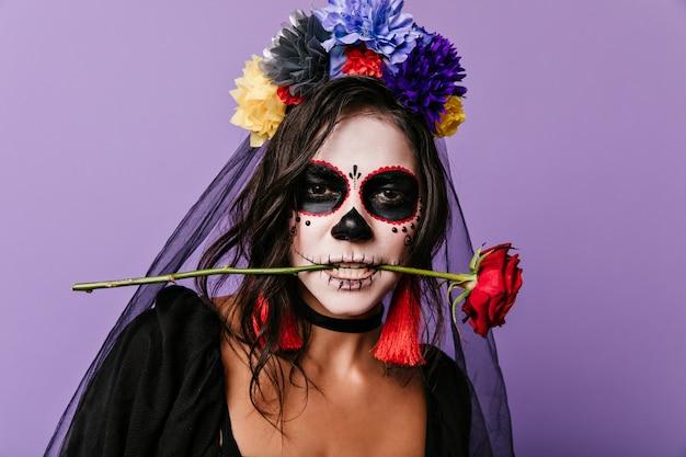 Leidenschaftliche mexikanerin mit gemaltem gesicht, das rote rose in ihren zähnen hält. nahaufnahmefoto der lockigen brünette mit den bunten blumen in ihren haaren.