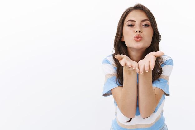 Leidenschaftliche sinnlich gut aussehende moderne kaukasische frau schlanke kamera zum küssen, bläst luft muah händchen haltend in der nähe von schmollenden lippen, um eine romantische und alberne kokette nachricht zu senden