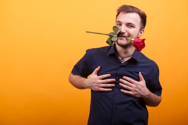Leidenschaftlicher junger mann, der rote rose im mund über gelbem hintergrund hält. junge liebe
