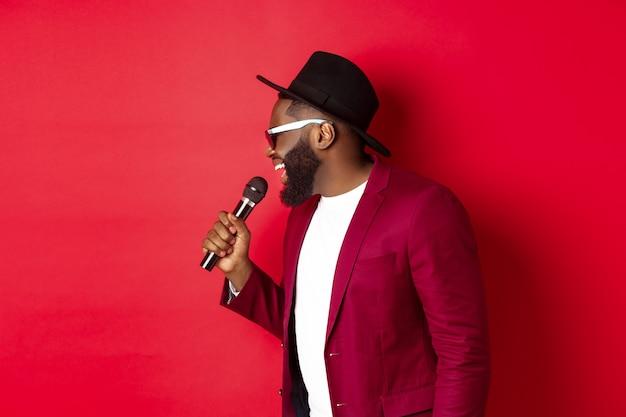 Leidenschaftlicher schwarzer sänger, der vor rotem hintergrund auftritt, in das mikrofon singt, party-outfit trägt und über rotem hintergrund steht.