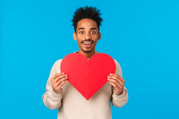 Leidenschaftlicher und aufgeregter afroamerikanerkerl in der liebe, die soulmate sein herz gibt, nach anderer hälfte sucht, herzvalentinsgrußcad hält und als ausdrückliche neigung, blau lächelt