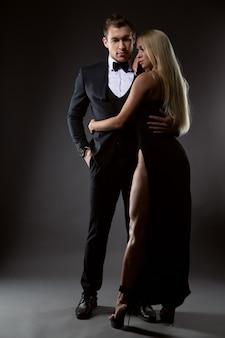 Leidenschaftliches paar: eine frau mit heller frisur im schwarzen abendkleid und ein gutaussehender mann im anzug mit fliege posieren in einem dunklen studio