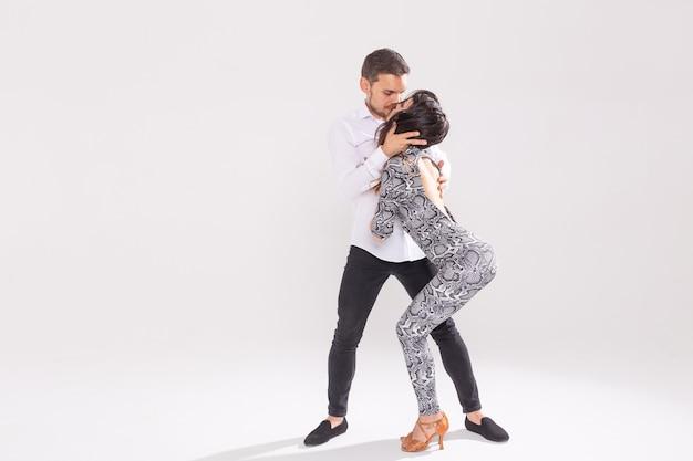 Leidenschaftliches paar tanzt social danse kizomba oder bachata oder semba oder taraxia auf weißem hintergrund mit kopierraum