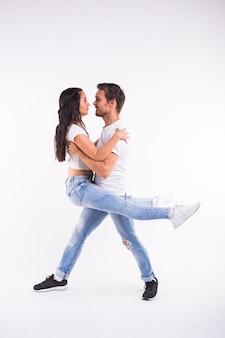 Leidenschaftliches paar tanzt social danse kizomba oder bachata oder semba oder taraxia auf weißem hintergrund.