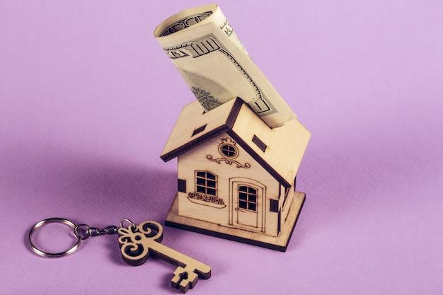 Leihen oder sparen sie für den kauf eines haus- und immobilienkonzepts. hypothekenlade- und rechner-eigenschaftsdokumentkonzept. holzhaus steht mit schlüssel und dollar.