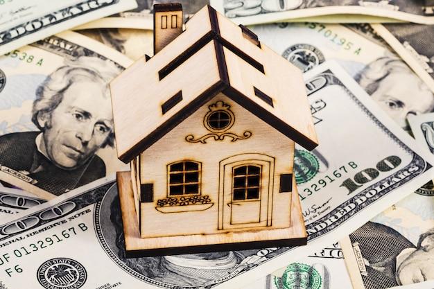 Leihen sie oder sparen sie für kauf ein haus- und immobilienkonzept. hypothekenladen und taschenrechner-eigentumsdokumentenkonzept. holzhaus steht auf dollar