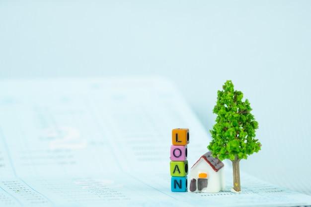 Leihtext und kleines musterhaus und bäumchen mit notizbuch