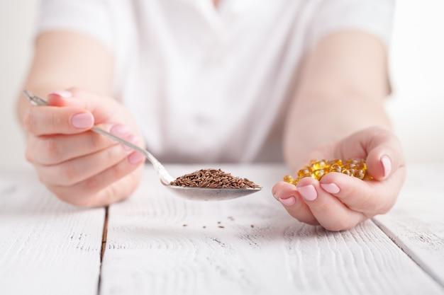 Leinöl und leinsamen. selektiver fokus in weiblichen händen