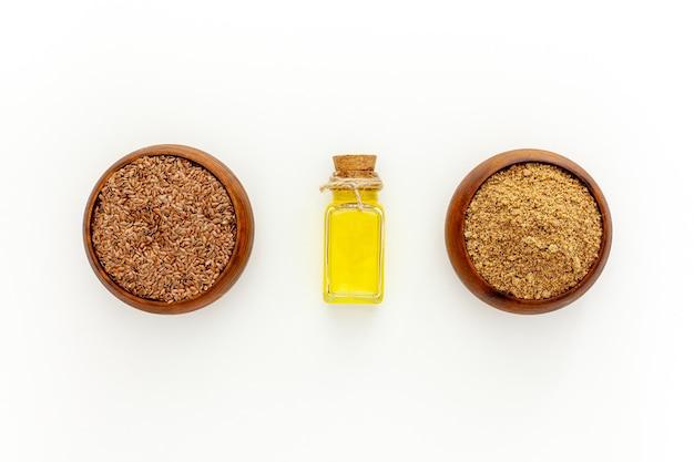 Leinsamen in einem löffel und einer schüssel mit einer flasche leinsamenöl und leinsamenmehl