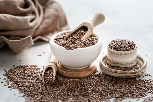 Leinsamen in einer keramikschale mit einem holzlöffel. bio gesunde lebensmittel.