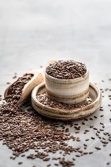 Leinsamen in keramikschale mit holzlöffel isoliert. bio gesunde lebensmittel. vertikales foto