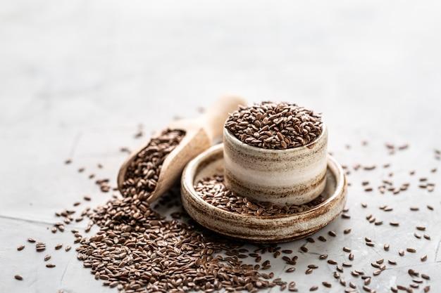 Leinsamen in keramikschale mit holzlöffel isoliert. bio gesunde lebensmittel.