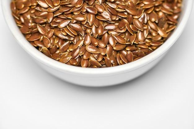 Leinsamen, leinsamen in schüssel, isoliert. bund linum usitatissimum - gewöhnlicher leinsamen. gesunder vegetarischer ernährungszusatz für die ernährung.