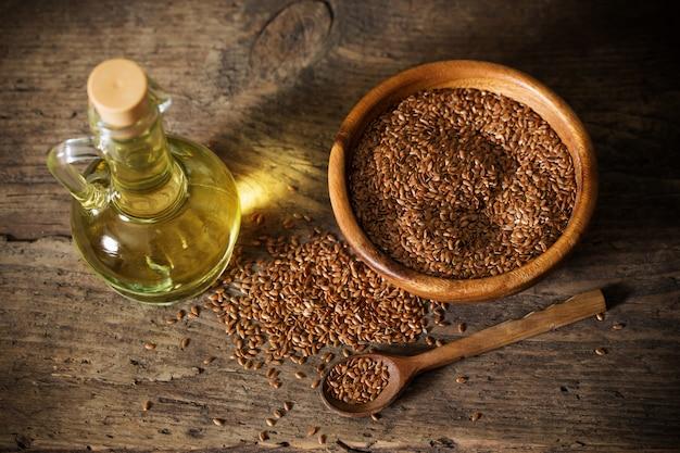 Leinsamen und leinöl in einem glaskrug auf einem holztisch