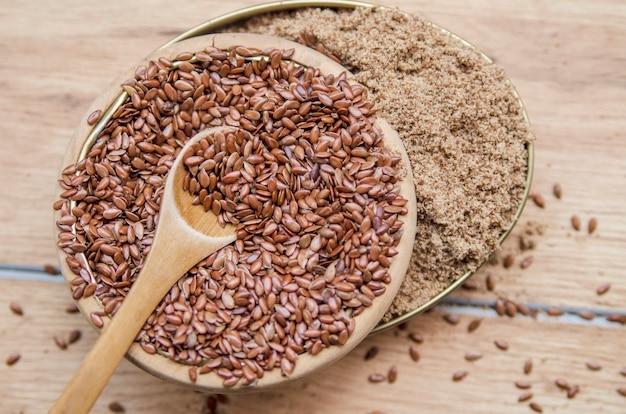 Leinsamenkorn und gemahlener flachs im hölzernen kleinen löffel und in der schüssel natürliches getreide