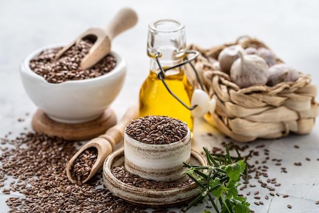 Leinsamenöl in einer flasche und keramikschale mit braunen leinsamen und holzlöffel auf einem weißen