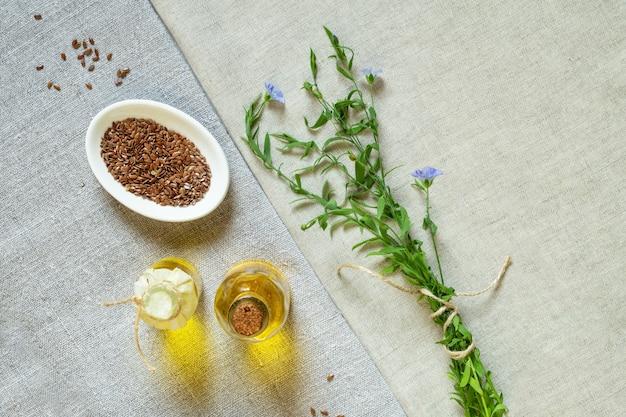 Leinsamenöl, samen und blühender flachs auf leinentuch