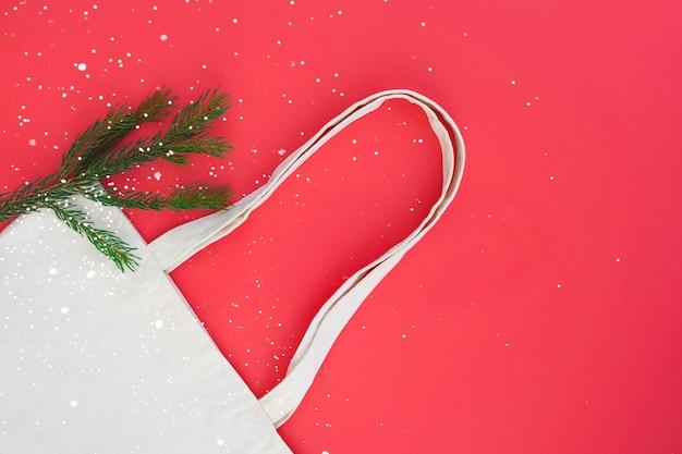 Leinwand baumwolle weiße tasche und zweig des weihnachtsbaums auf dem leuchtend roten hintergrund
