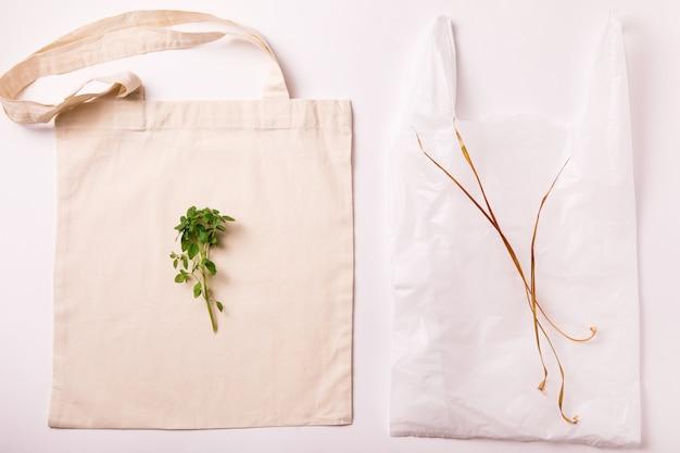 Leinwand umweltfreundliche einkaufstasche aus baumwolle und plastiktüte über weiß