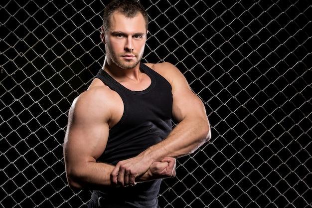 Leistungsfähiger kerl, der seine muskeln auf zaun zeigt