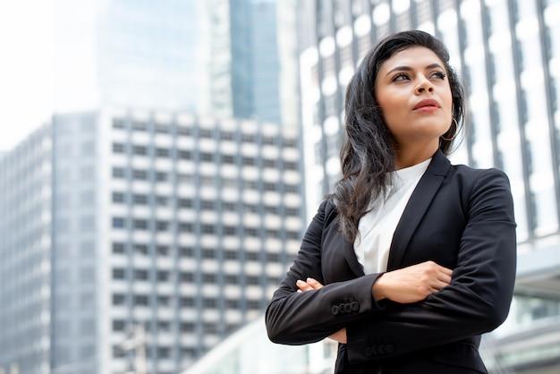 Leistungsfähiger lateinischer geschäftsfrauführer, der mit dem arm gekreuzt steht