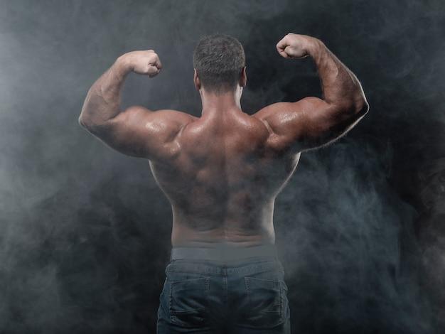 Leistungsfähiger muskulöser mann zeigt bizeps auf schwarzem. kraft- und fitnesskonzept