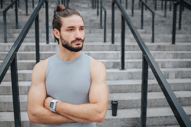 Leistungsfähiger und muskulöser junger mann steht und wirft auf kamera auf