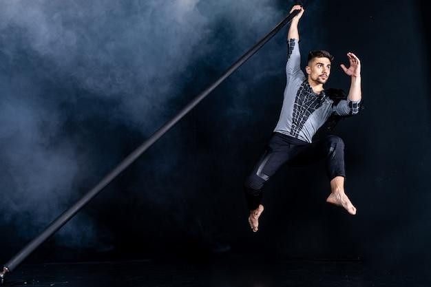 Leistungskonzept. mann, der an chinesischer stange hängt. athlet, der fliegende stange ausführt.