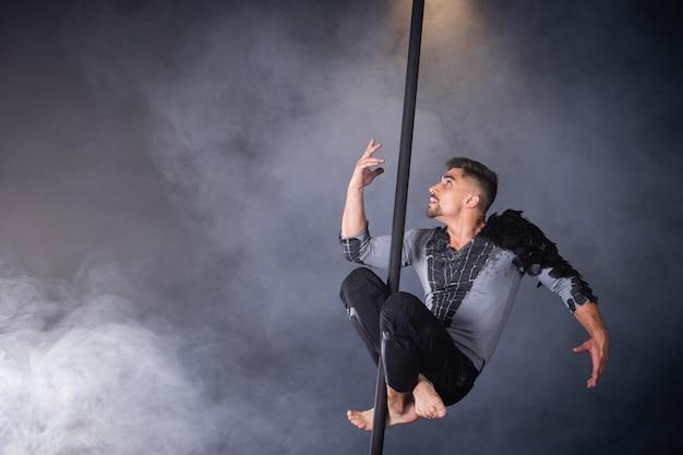 Leistungskonzeptmann, der an chinesischem pole-athlet hängt, der fliegende pole durchführt