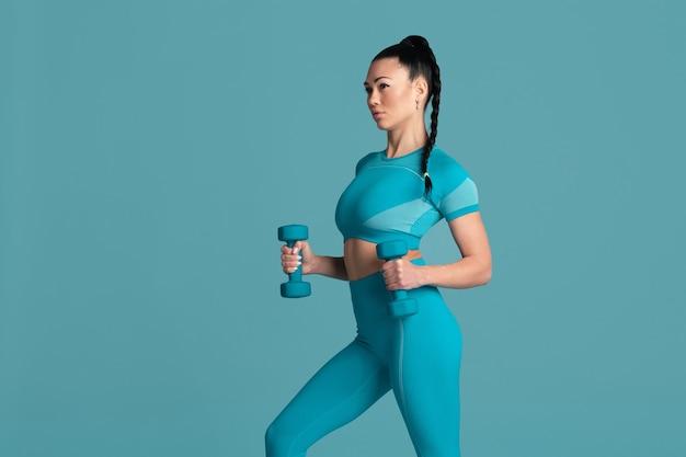 Leistungsstark. schöne junge sportlerin üben, einfarbiges blaues porträt. brünettes modell mit sportlicher passform und gewichten. bodybuilding, gesunder lebensstil, schönheits- und aktionskonzept.