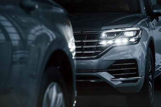 Leistungsstarke scheinwerfer. partikelansicht von modernen luxusautos, die tagsüber drinnen geparkt sind