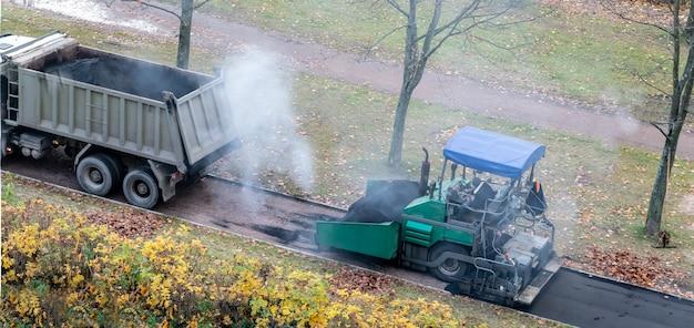 Leistungsstarker gleisfertigerständer auf der parkzone. asphaltfertiger, pflastermaschine, schwere industriemaschinen geparkt. asphaltverlegemaschine