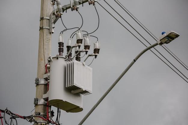 Leistungstransformator auf mast mit hochspannungsdrähten