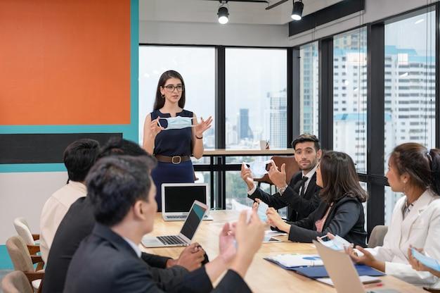 Leitende frau, die gesichtsmaske mit der präsentation einer neuen unternehmensrichtlinie in neuem normalem büro während des multiethnischen treffens hält