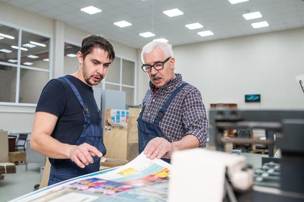 Leitender angestellter in gläsern, der papier berührt und mit kollegen über gedruckte seiten in der druckerei spricht