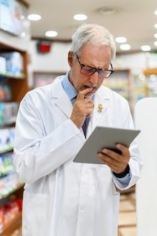 Leitender apotheker, der an tablette in seinem geschäft arbeitet