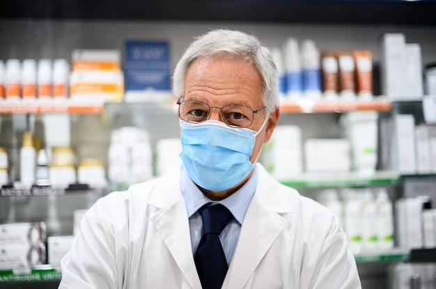 Leitender apotheker, der aufgrund einer coronavirus-pandemie in seinem geschäft eine maske trägt